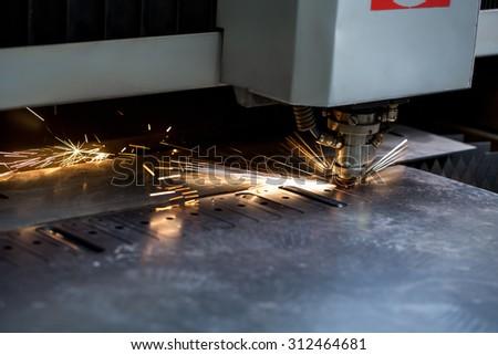 Modern automated machine laser cutting metal sheet - stock photo