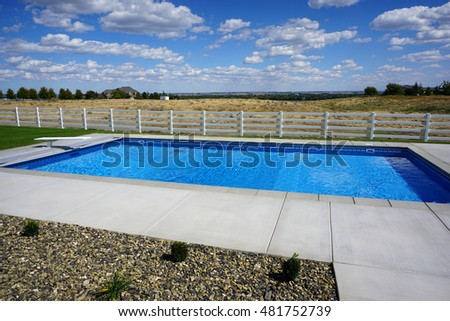 modern backyard swimming pool with fence and open space