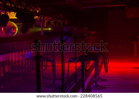 Modern bar interior decor and colorful red and purple strobe lighting illuminating a row of stylish bar stools at a counter
