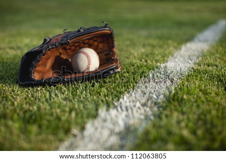 Modern baseball glove with ball in the grass near stripe in the field