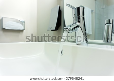 Modern bathroom chrome faucet with running water - stock photo