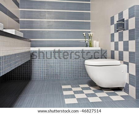Modern bathroom in blue and gray tones with toilet and mosaic - stock photo