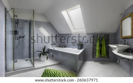 Modern bathroom in cool style with glass shower and bathtub in the attic of a house - stock photo
