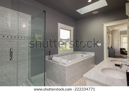 Modern bathroom interior in marble with glass door shower and window. - stock photo