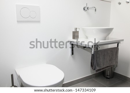 Modern bathroom interior with a wall mounted tap and ceramic hand basin and toilet - stock photo