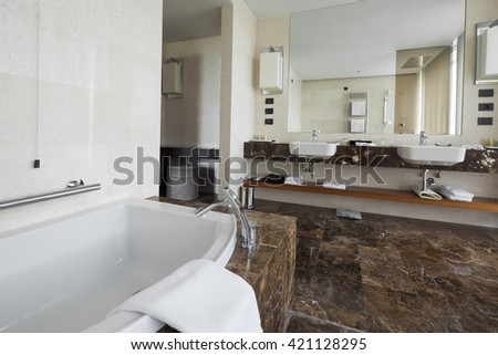 Modern bathroom interior with double sink and large mirrors, bath tub, tiles, view window and towels. - stock photo