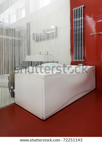 Modern bathroom interior with hydro massage bathtub and red ceramic tiles