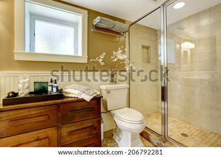 Modern bathroom interior with wooden cabinet, glass door shower and washbasin stand