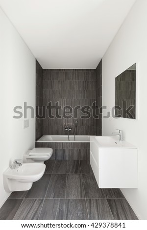modern bathroom of new apartment, white walls and gray tiles - stock photo
