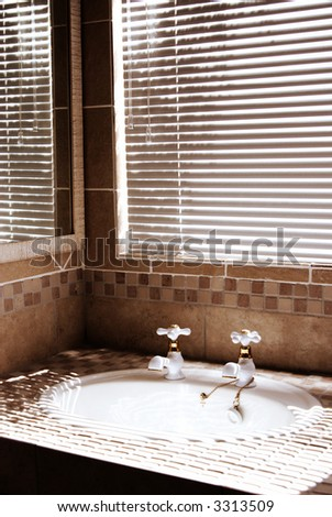 Modern bathroom with blinds on the window. Shot in the morning, with bright sun coming through the blinds. Artistic grain added to dramatize the interior. - stock photo