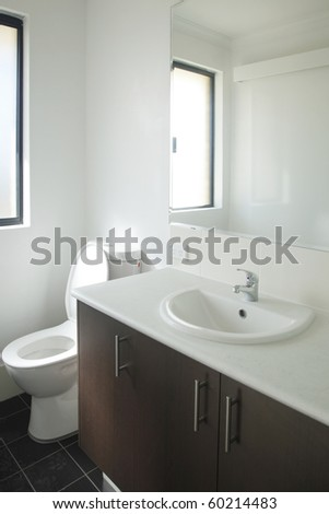 Modern bathroom with bright colours and dark cupboard - stock photo