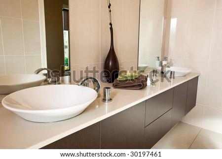 Modern bathroom, with double round basins.  Earthy warm tones. - stock photo