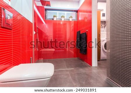 Modern bathroom with marble floor and shower on red wall - stock photo
