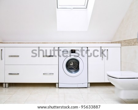 Modern bathroom with shiny white cabinets and washing machine - stock photo