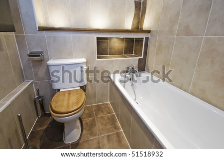 modern bathroom with white ceramic suite and stone tiles - stock photo