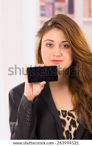 modern beautiful young woman holding cell phone looking at the camera - stock photo