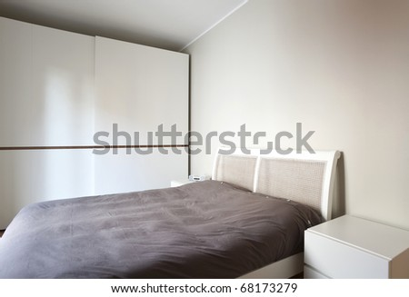 modern bedroom, double bed and wardrobe - stock photo