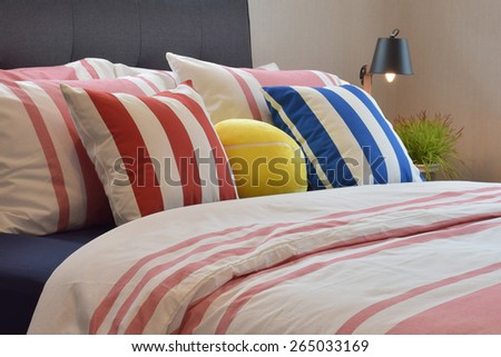Modern bedroom interior with colorful pillows and reading lamp on bedside table - stock photo