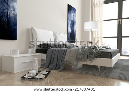 Modern bedroom interior with double divan bed covered in rugs and throws in grey and white decor with a breakfast tray on the floor alongside and a window behind