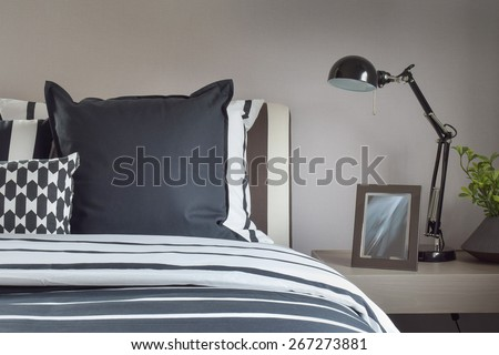 Modern bedroom interior with pillows and reading lamp on bedside table - stock photo