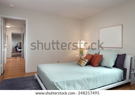 Modern Bedroom of holiday villa with blue bed cover and color mixed pillows. - stock photo