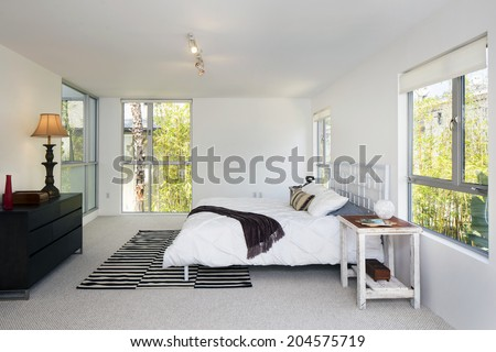 Modern bedroom surrounded by greenery interior with bed frame and view windows. - stock photo