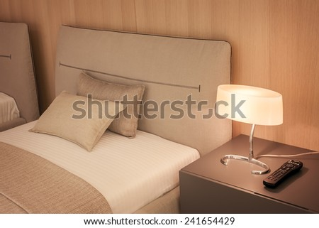Modern Bedroom with a bed and night-light in hotel or motel. - stock photo