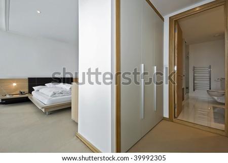 modern bedroom with a walk in wardrobe and en-suite bathroom - stock photo