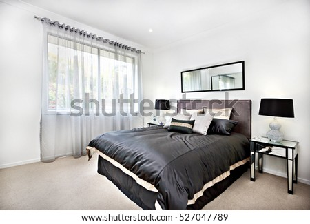 Modern bedroom with black decoration and mirror beside lamps including blanket and pillows beside the glass tables, there is a curtain covered the window with the sunlight spread