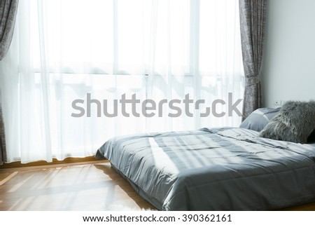 modern bedroom  with bright window in a loft. - stock photo
