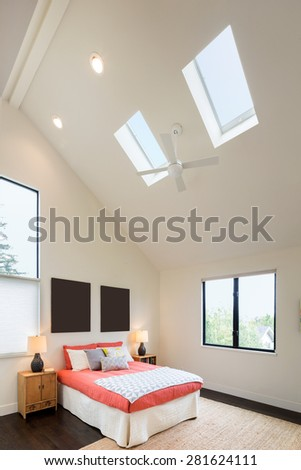 Modern bedroom with high ceiling, red bed sheet cover and pillows. - stock photo