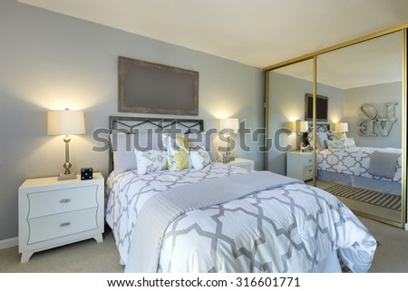 Modern bedroom with matching elegant decoration with large mirror.  - stock photo