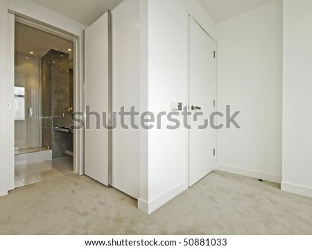 modern bedroom with walk-in wardrobe and en-suite bathroom - stock photo