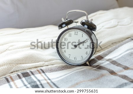 modern black alarm clock on bed in bedroom at home