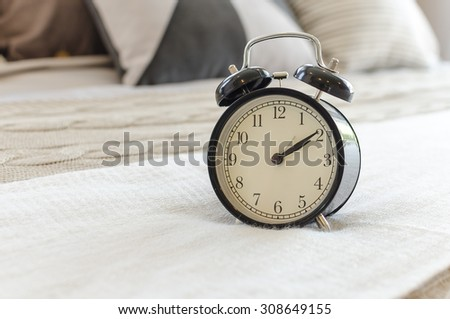 modern black alarm clock on bed with white blanket