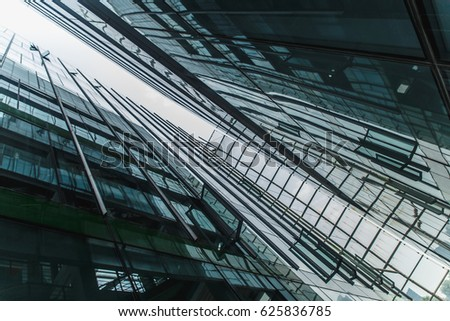 Modern black and dark blue glass skyscrapers background. Business construction concept of successful industrial solid. Glass steel architecture.