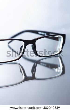 Modern black eyeglasses on glass surface against gray background
