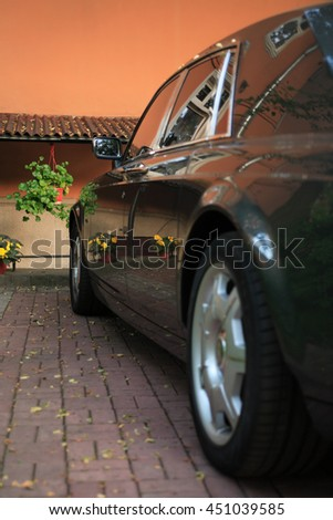 Modern black limousine parking in courtyard near wall