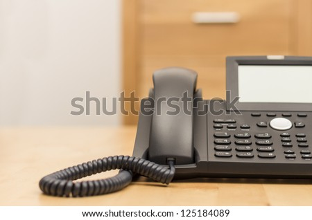 modern black phone on wooden desk with blurred background