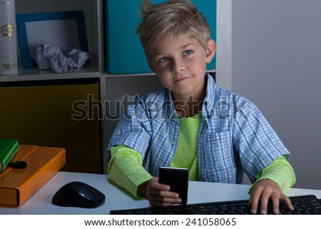 Modern blonde child using phone and computer