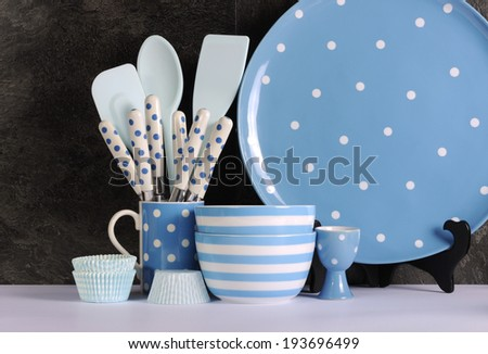 Modern Blue and White Polka Dot Kitchen with large platter plate, cutlery and kitchenware against black slate and white benchtop. - stock photo