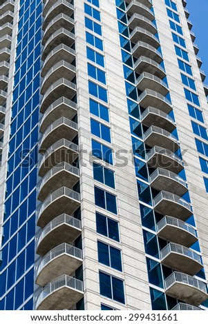 Modern blue glass and white stone condo tower - stock photo