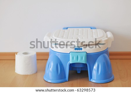 Modern blue training pot and roll of wc paper - stock photo