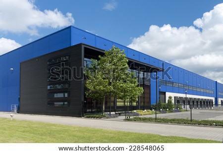 modern blue warehouse in the Rotterdam harbor area - stock photo