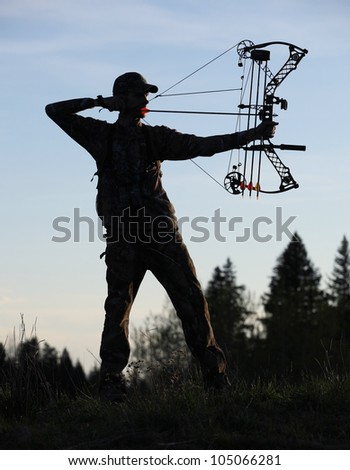modern bow hunter silhouette in the woods - stock photo