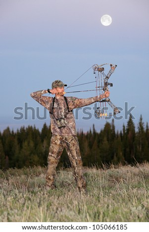 modern bowhunter drawing bow at dusk - stock photo