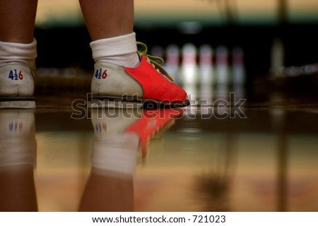 Modern bowling shoes have bright colors. A low angle shot right along the alley showing shoes and their reflection in the highly polished wood. Focus is on bowler's shoes - stock photo