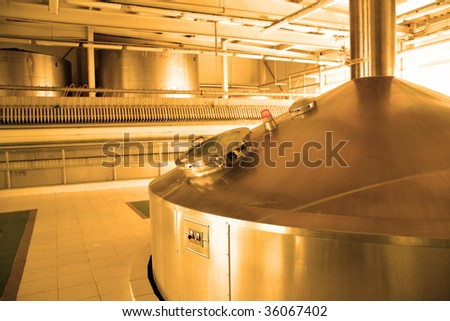 Modern brewery - workshop with steel fermentation tanks - stock photo