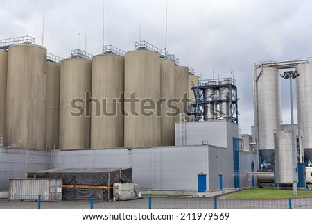 Modern brewery yard against cloudy sky - stock photo