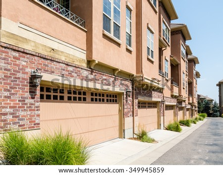 Modern brick and stucco condo buildings with balconies and garages - stock photo